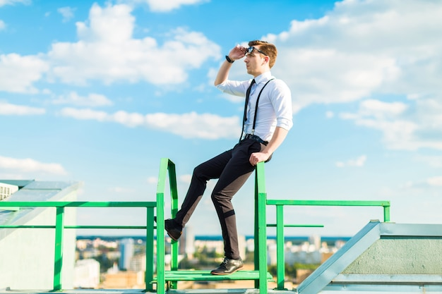 Busunessman jovem de camisa branca, gravata, aparelho e óculos de sol fica na escada do telhado Foto Premium