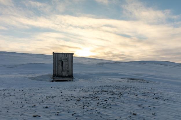 Cabana de madeira pequena da casinha no meio da paisagem ártica no inverno Foto Premium