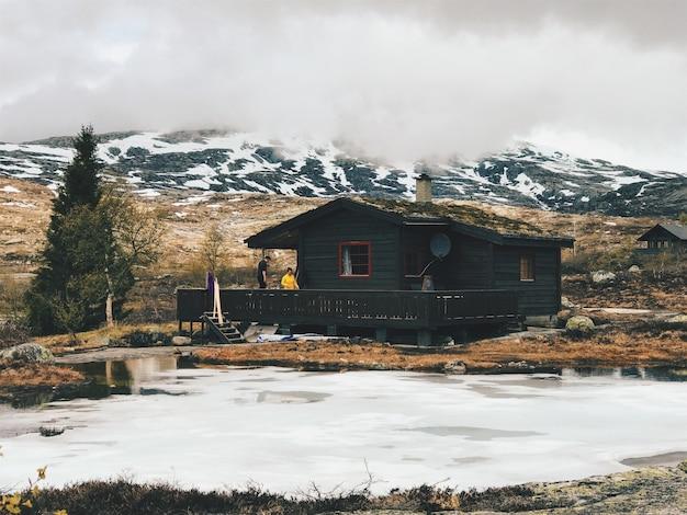 Cabana solitária fica diante das montanhas cobertas de neve Foto gratuita
