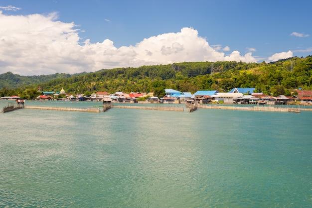 Cabanas da vila e do palafitas em tentena no lago poso em sulawesi central, indonésia Foto Premium