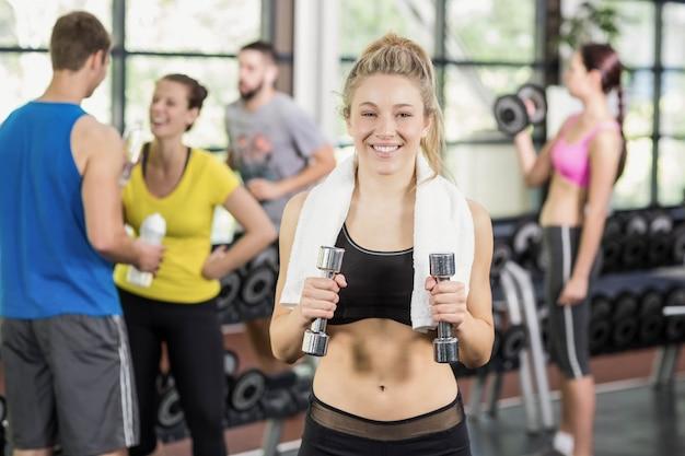 Cabe a mulher posando com mulheres atléticas e o homem por trás no ginásio crossfit Foto Premium