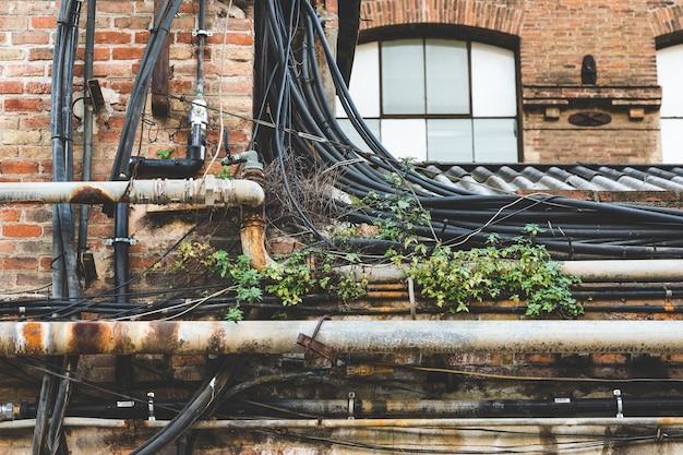 Cabeamento e ervas daninhas no telhado de uma antiga fábrica Foto Premium