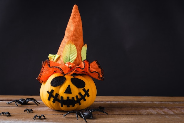 Cabeça de abóboras fantasma jack lanterna sorriso assustador usar chapéu e aranha na mesa de madeira Foto Premium