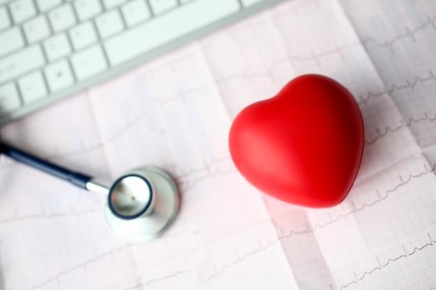 Cabeça de estetoscópio médico e coração de brinquedo vermelho Foto Premium