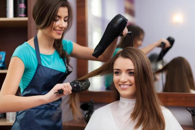 Cabeleireira usando escova e secador de cabelo Foto gratuita