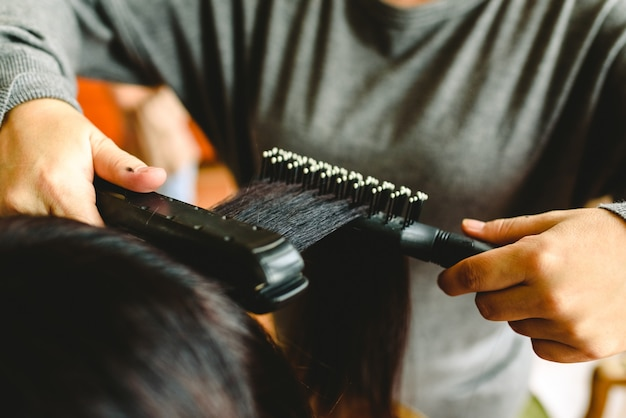 Cabeleireiro alisando o cabelo de uma mulher com um alisador de cabelo. Foto Premium