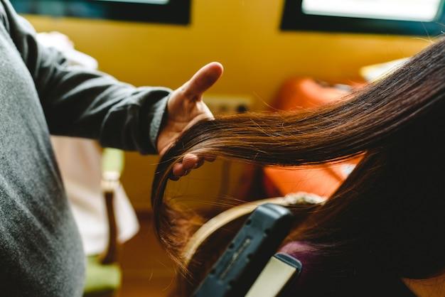 Cabeleireiro alisando o cabelo escuro de um cliente. Foto Premium
