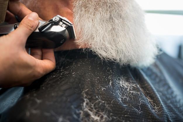 Cabeleireiro aparar barba com barbeador elétrico para o cliente Foto gratuita