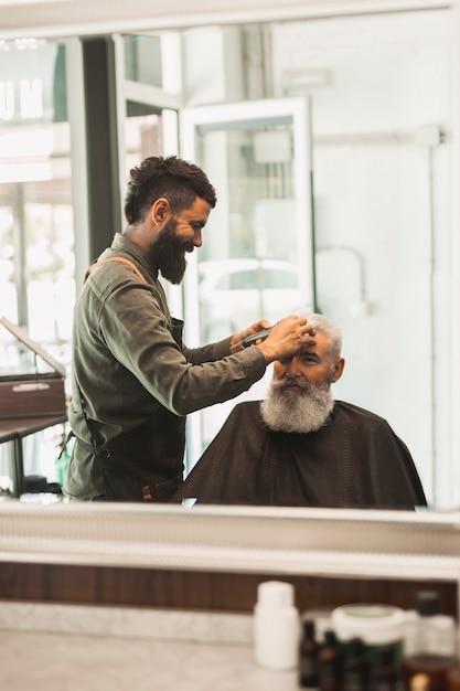 Cabeleireiro aparar o cabelo para macho envelhecido no salão Foto gratuita