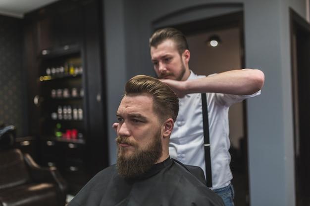 Cabeleireiro bonito estilo de cabelo do cliente Foto gratuita