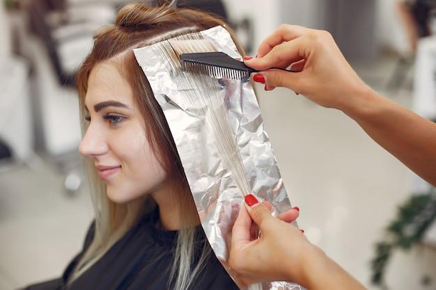 Cabeleireiro cabelo colorido seu cliente em um salão de cabeleireiro Foto gratuita