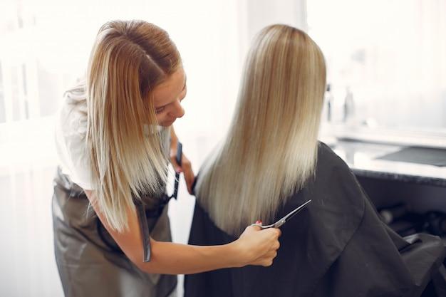 Cabeleireiro cortar o cabelo de seu cliente em um salão de cabeleireiro Foto gratuita