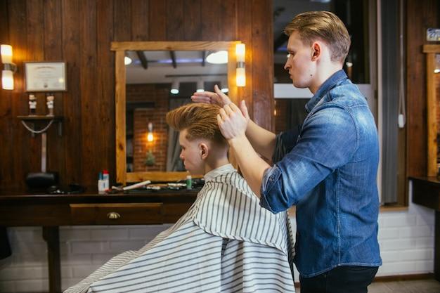 Cabeleireiro de cortes de cabelo de menino ruivo adolescente na barbearia Foto Premium