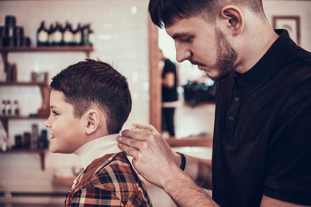 Cabeleireiro de homem corta o bebê na barbearia. Foto Premium
