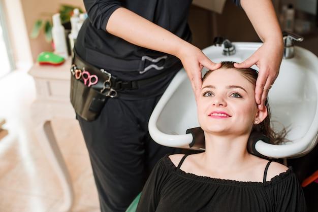 Cabeleireiro e mulher durante a lavagem do cabelo Foto Premium
