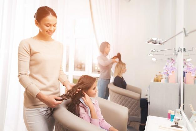 Cabeleireiro fazendo o estilo de cabelo para uma pequena garota de cabelos escuros. Foto Premium