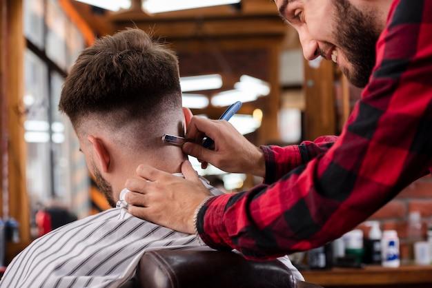 Cabeleireiro fazendo os ajustes finais do corte de cabelo Foto gratuita