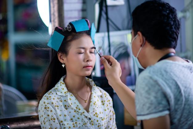 Cabeleireiro feminino em pé, maquiagem de rosto e fazer penteado bonito adorável jovem no salão de beleza Foto gratuita