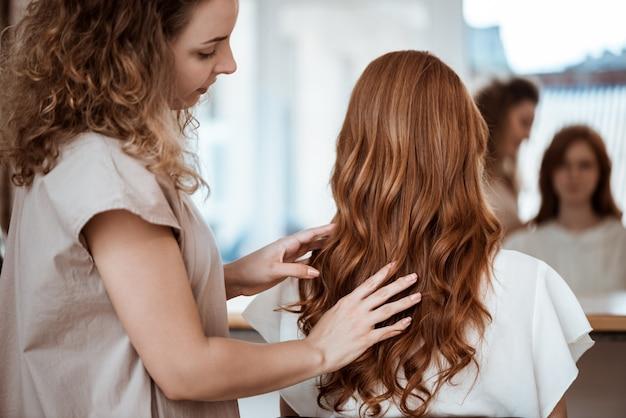 Cabeleireiro feminino fazendo penteado para mulher ruiva no salão de beleza Foto gratuita