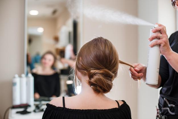 Cabeleireiro, fixação de cabelo de mulher com spray de cabelo Foto Premium
