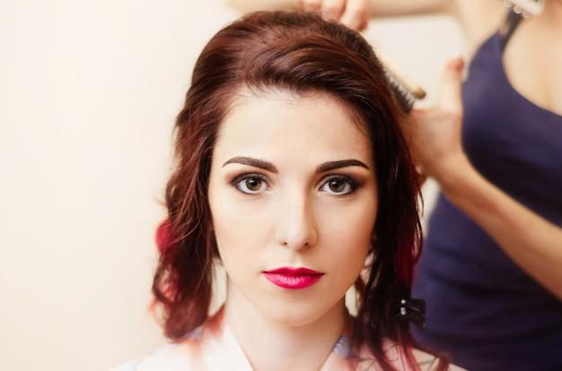 Cabeleireiro funciona. o estilista torce o cabelo que passa para a menina com cabelo vermelho. Foto Premium