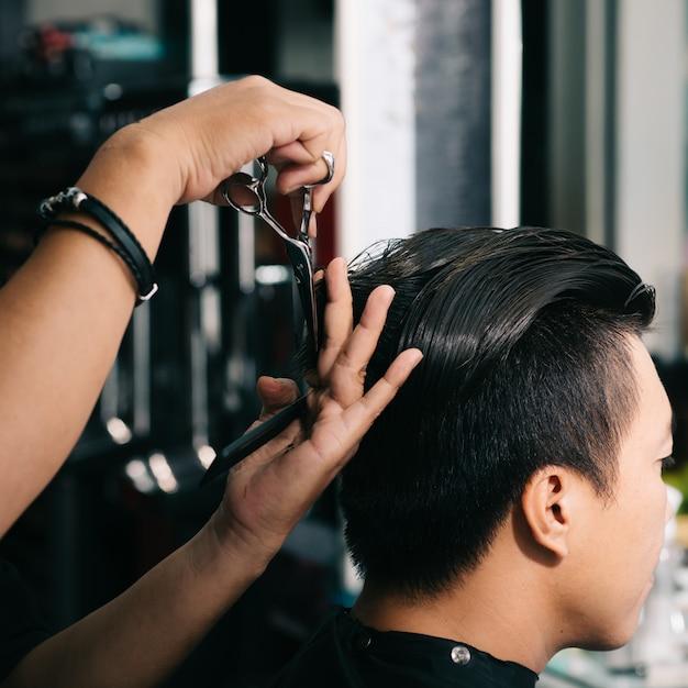 Cabeleireiro irreconhecível, corte o cabelo do cliente masculino asiático com uma tesoura no salão Foto gratuita
