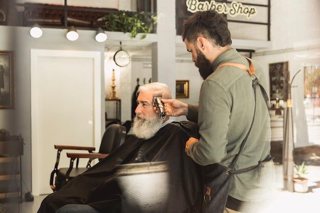 Cabeleireiro masculino trabalhando com cabelo de cliente idoso Foto gratuita