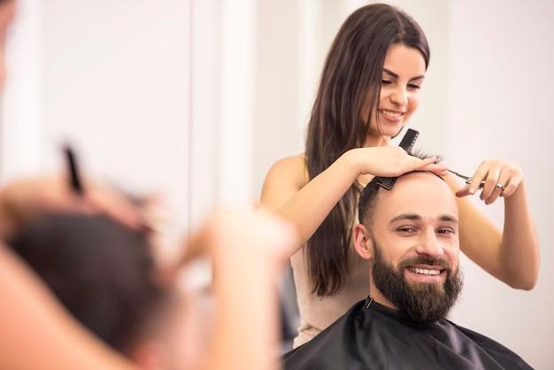 Cabeleireiro mulher está cortando cabelo de homem. Foto Premium