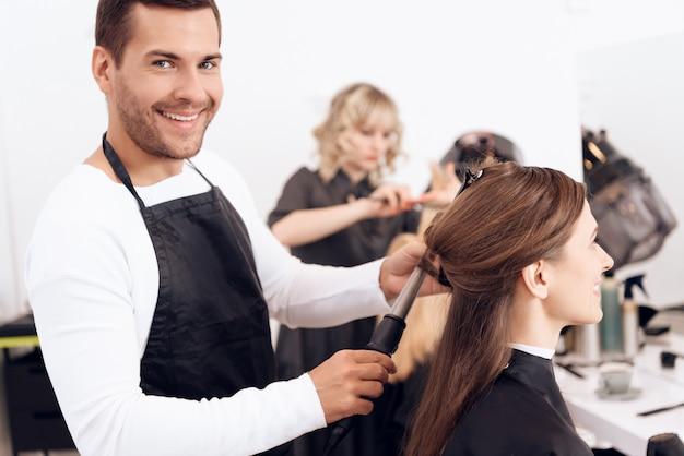 Cabeleireiro, ondulando o cabelo castanho da mulher bonita. Foto Premium