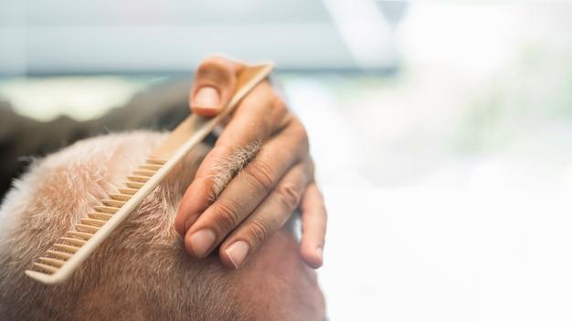 Cabeleireiro, penteando o cabelo para o cliente na barbearia Foto gratuita