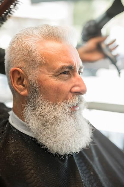 Cabeleireiro sem rosto fazendo cabelo estilo masculino cliente Foto gratuita