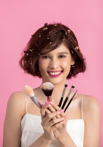 Cabelo curto asiático jovem mulher bonita aplicar escova de pó cosmético Foto gratuita