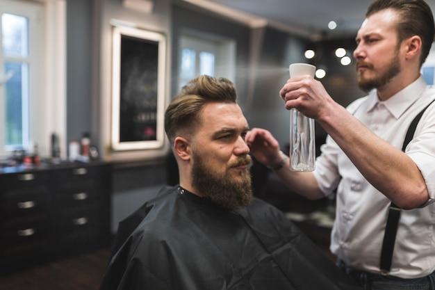 Cabelo de pulverização do barbeiro do cliente Foto gratuita
