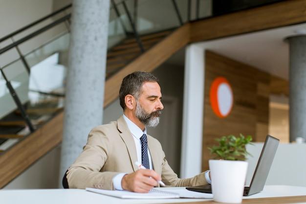 Cabelo grisalho senior empresário trabalhando no laptop no escritório moderno Foto Premium