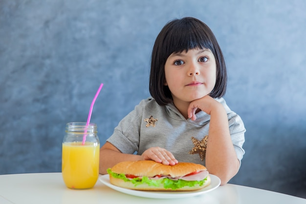Cabelo preto bonito menina tomando café da manhã e bebendo suco de laranja em casa Foto Premium
