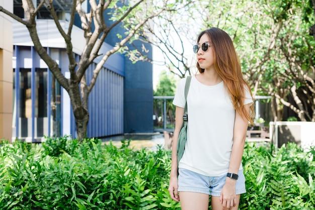 Cabelos longos de menina asiática hipster em branco em branco t-shirt está de pé no meio da rua Foto gratuita