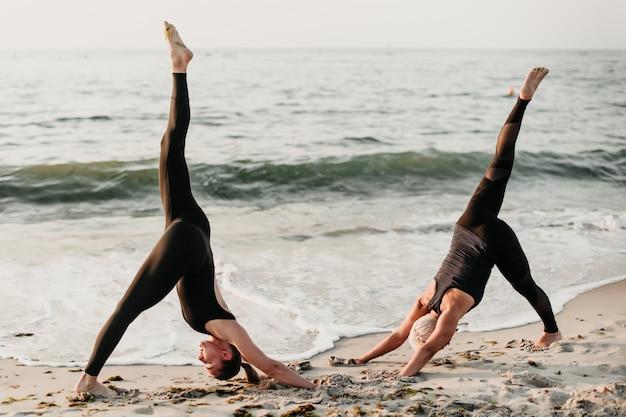 Cabem as mulheres fazendo exercícios de ioga em sincronização na praia perto do mar Foto Premium