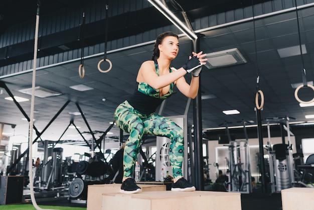 Caber a caixa de jovem mulher sexy pulando em um ginásio de estilo crossfit. atleta feminina está realizando saltos de caixa no ginásio. Foto Premium