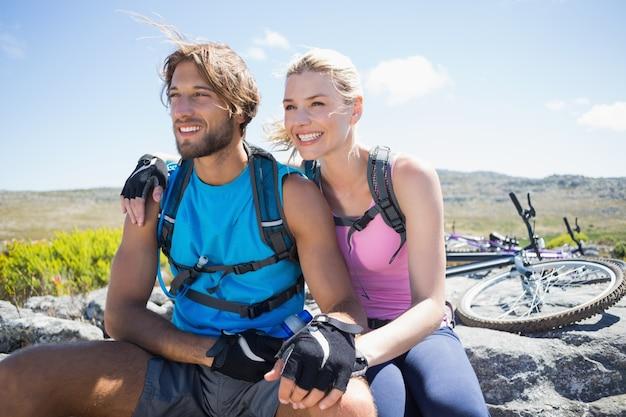 Caber ciclista casal fazendo uma pausa no pico rochoso em um dia ensolarado Foto Premium