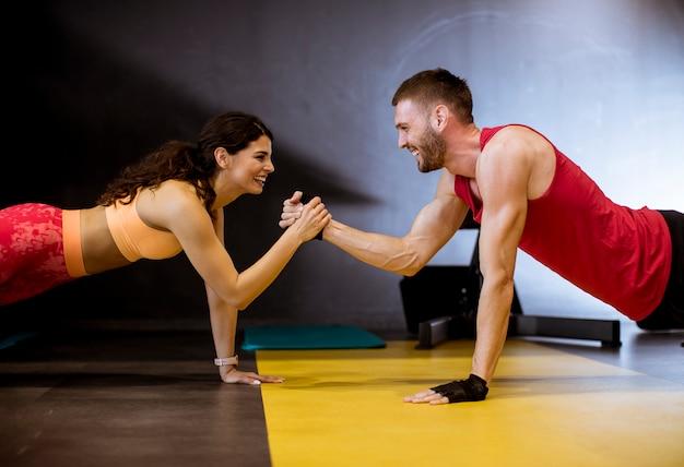 Caber esportiva homem e mulher fazendo exercício de núcleo de prancha Foto Premium
