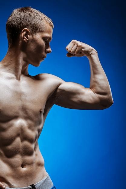 Caber jovem com belo torso na parede azul Foto gratuita