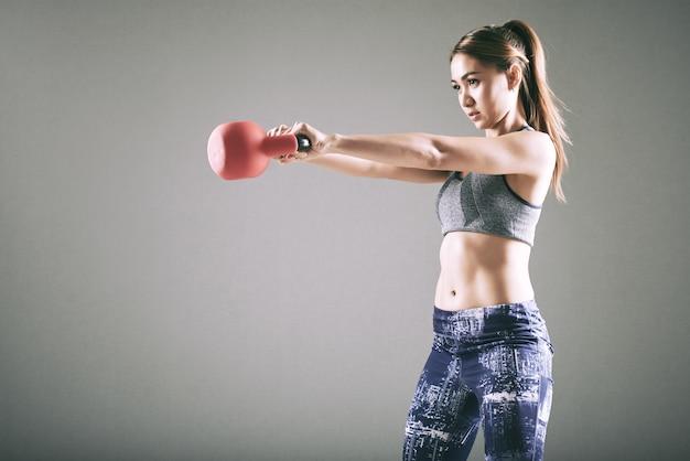 Caber jovem mulher asiática, exercitar-se com kettlebell Foto gratuita