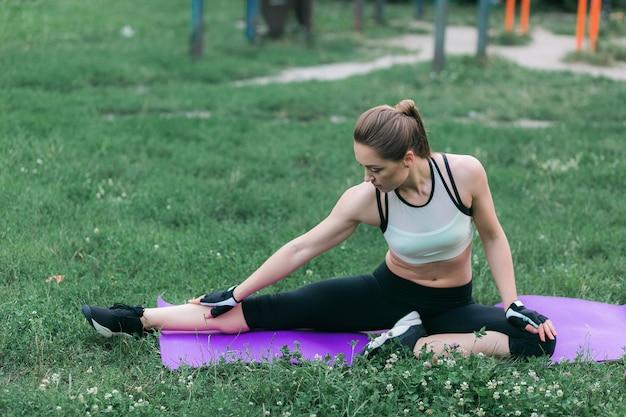 Caber jovem no sportswear realiza alongamento depois de um trabalho fora Foto gratuita