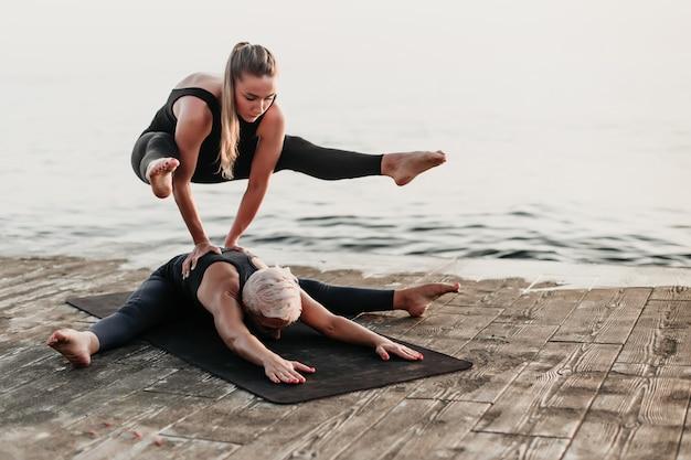 Caber mulher desportiva fazendo parada de mãos em acro yoga asana na praia perto do mar Foto Premium