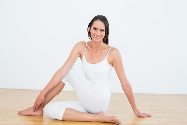 Caber mulher fazendo a meia torção da coluna vertebral no estúdio de fitness Foto Premium
