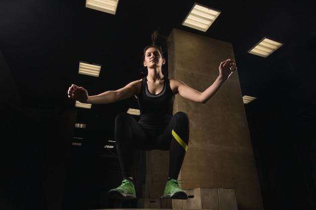 Caber mulher fazendo caixa pulando no ginásio crossfit Foto Premium