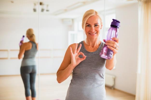 Caber mulher idosa segurando uma garrafa de água Foto gratuita