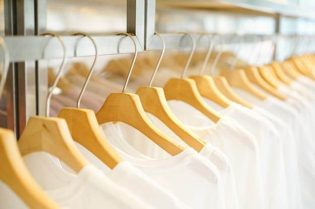 Cabide de madeira com t-shirt branca na loja de moda mulher Foto Premium