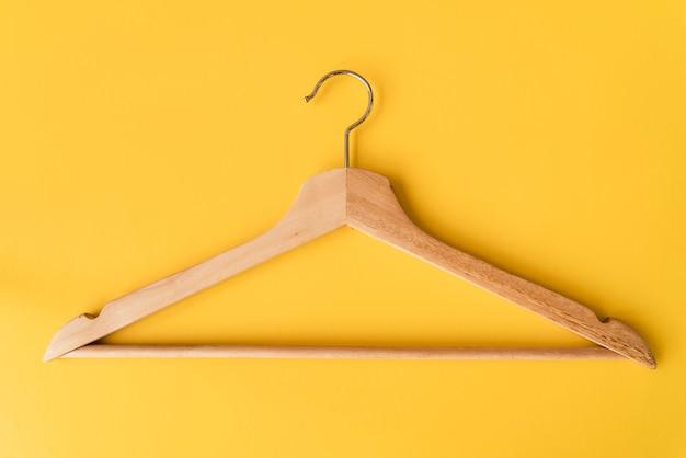Cabide de madeira vista superior com fundo amarelo Foto gratuita