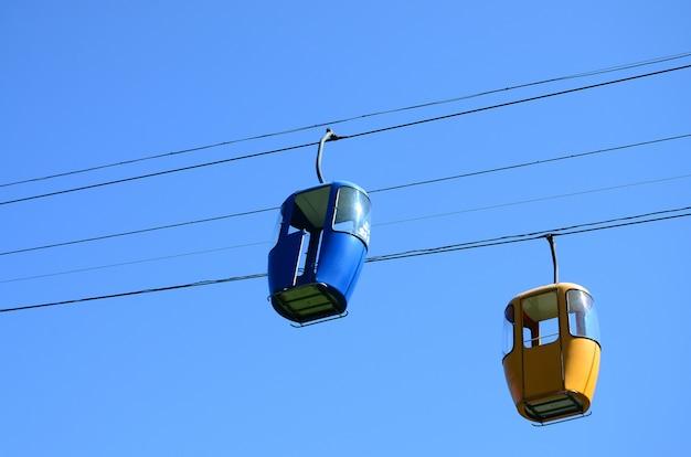 Cabines de caminho de cabo de passageiro azul e amarelo no céu claro Foto Premium